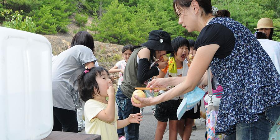 おいしそうに桃を食べる子供の写真